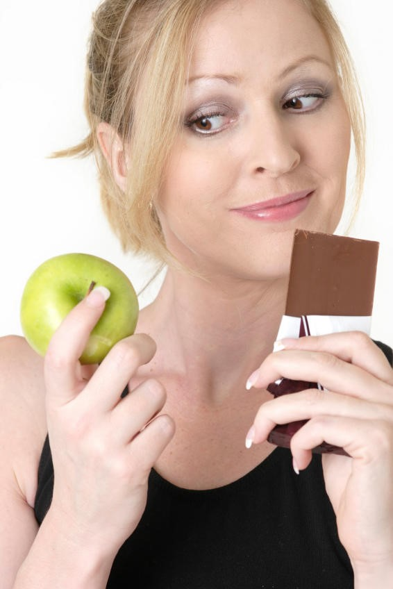 Women holding apple and chocolate