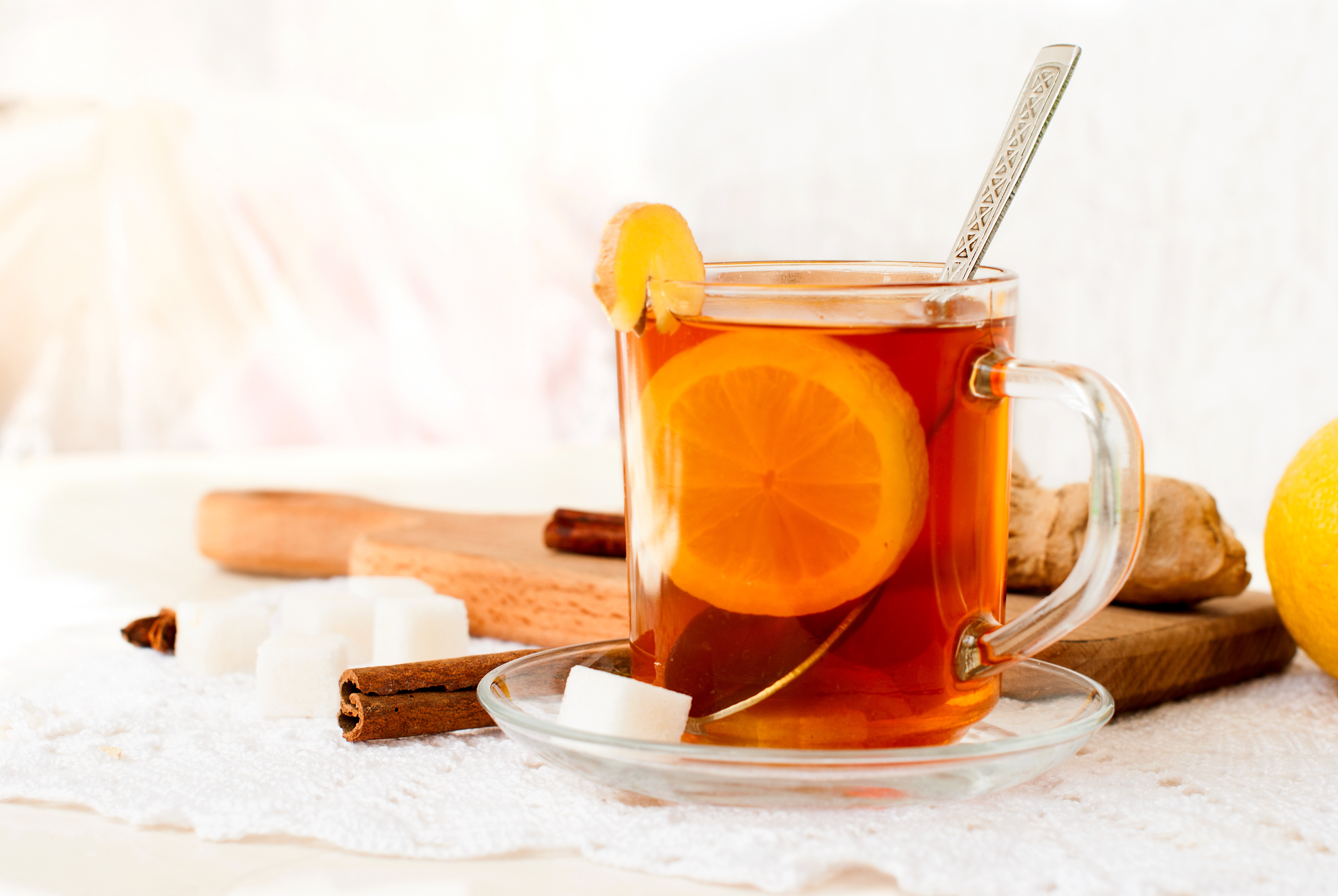 cup of tea with ginger, lemon slice and cinnamon stick. lemon and ginger root on the board
